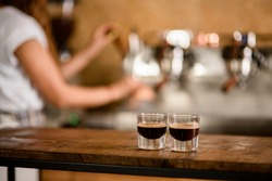 view of two transparent glasses of freshly brewed espresso on wooden table at blurred background. Selective focus.