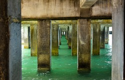 View of under the concrete pier with turquoise sea at seaside of tropical island. Abstraction of bridge with sea water and leading lines. Scene from under the harbor with a lot of concrete pillar.