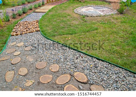 View of unusual garden path made as massage road for feet (different waste: wooden cubes, plastic bottles, small stones, round cuts of trees, etc.). Folk medicine, acupuncture. Selective focus