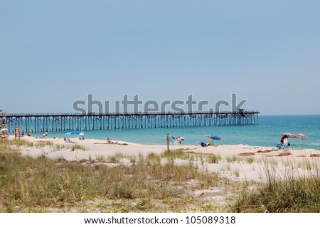 View of vacationers relaxing on a white sandy beach that has a long wooden pier in the beautiful turquoise ocean water.