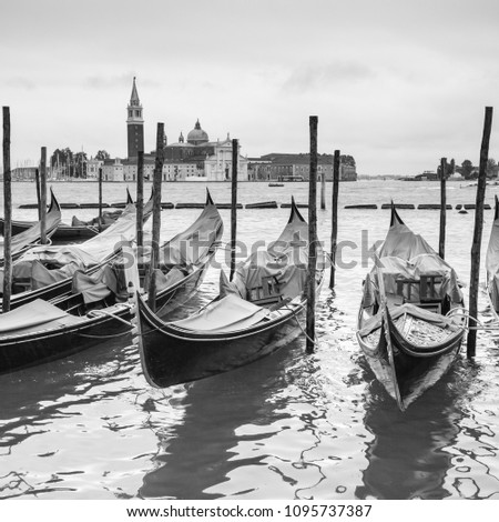View of venetian lagoon with moored gondolas, Venice, Italy. Black and white image
