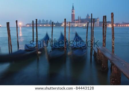 View of Venice, Italy at dusk - three gondolas in front of the San Giorgio Maggiore island