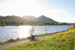 View of Vienna's Leopoldsberg and the danube river from danube island in the evening sun in summer, with a person on a bike on the  bike path on danube island