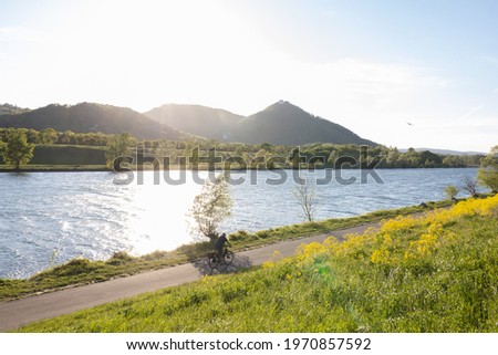 View of Vienna's Leopoldsberg and the danube river from danube island in the evening sun in summer, with a person on a bike on the  bike path on danube island Сток-фото ©