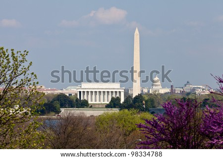 View of Washington DC skyline in late afternoon on a sunny day with Lincoln Memorial, Washington Monument and the Capitol with a blooming redbud