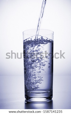 View of water being poured into a glass with a slice of lemon