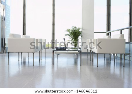 View of white armchairs and laptop in spacious and modern waiting room at office