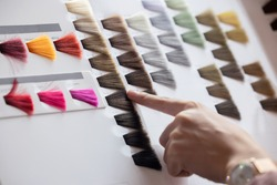 View of Woman Choosing Color from the Hair Color Chart  For Hair Dye Concept