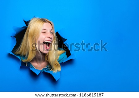 View of woman face through hole in blue paper. Winking smiling girl making hole in paper. Fashion and beauty concept. Copy space for advertising, to insert text or slogan. Discount, sale, season sales