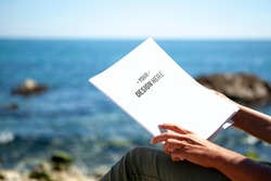 View of woman reading a magazine by the sea in the sun. With water and a blue sky in the background. Magazine cover mockup.