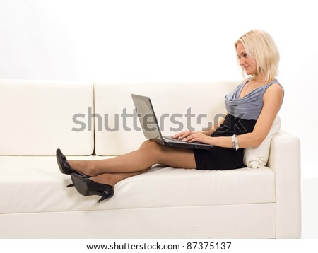 View of woman smiling while working on laptop