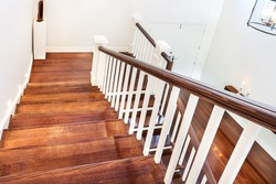 view of wooden glossy stairs from upword showing a beautiful scenery hunged on the wall