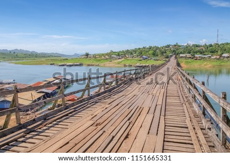 view of Wooden Mon Bridge with blue sky background,the officially named Uttama Nusorn Bridge cross the river, Sangklaburi, Kanchanaburi, Thailand