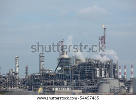 View of working oil refinery plant with  curling air emission smoke.