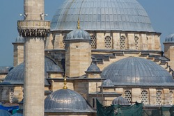View of Yeni Valide Camii Mosque from backstreets of Eminonu oldtown district in Istanbul Turkey, Ottoman style mosque built in 1597, located on Golden Horn and near Galata Bridge