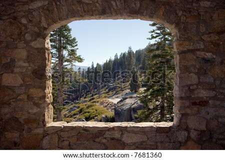 view of Yosemite National Park through the open stone window of a little hut