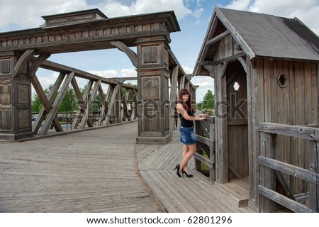 View of young, sexy woman, old-time bridge and watch box.