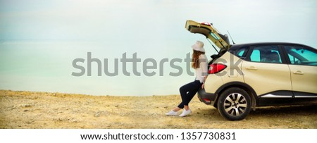 View of young woman traveler looking at sea sunset, sitting on hatchback car with the copy space. Banner.