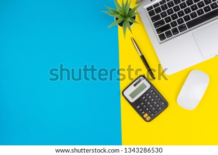 View office table desk. Workspace with calculator, mouse, black pen, laptop, decoration flower on blue and yellow background. Business, Finance, and Copy Space concept #1343286530
