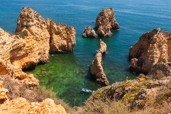 View on a bay with clean blue and green water framed by orange limestone cliffs with caves and boats on a sunny summer day, Algarve coast, south Portugal
