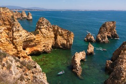 View on a bay with clean blue and green water framed by orange limestone cliffs with caves and small boats on a sunny summer day, Algarve coast, south Portugal