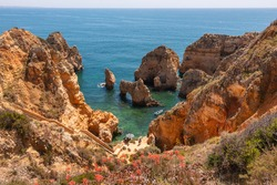 View on a bay with clean blue and green water framed by orange limestone cliffs with caves and boat on a sunny summer day, Algarve coast, south Portugal