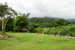 View on a campsite in rainforest near to river and mountains in cloudy weather. Chiang Dao, Thailand.