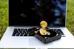 View on a laptop and a hard disk drive with a bitcoin representing cryptocurrencies on the grass on a sunny day.