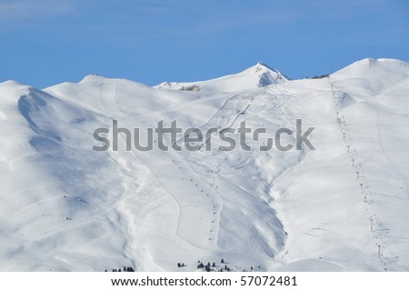 View on a steep skiing mountain with two slopes, skiers and lifts - shot in Livigno, Italian Alps - stock photo
