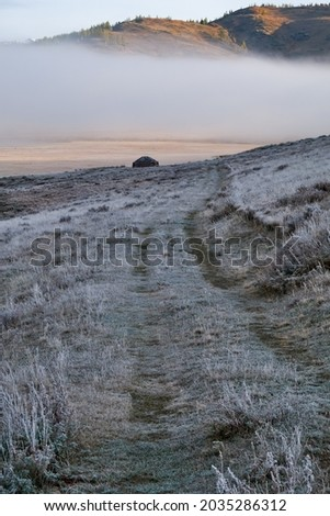 View on Altai shepherd's house ail and lake Dzhangyskol on mountain plateau Eshtykel. Hill with larch trees is on background. Morning fog over water. Hoarfrost is on the grass. Altai, Siberia, Russia Foto stock ©
