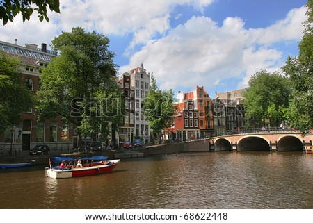 View on Amstel river (city canal) and historic houses in Amsterdam, Netherlands (Holland).