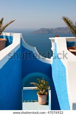 View on caldera and sea through blue arch, Santorini, Greece.