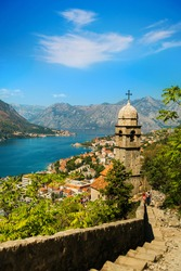 View on Church, ancient walls, mountains and sea in Kotor old town. Montenegro, Kotor bay. Top view