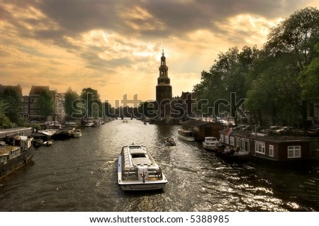View on city canal (Amstel river) with cruise ship in Amsterdam, Netherlands (Holland).