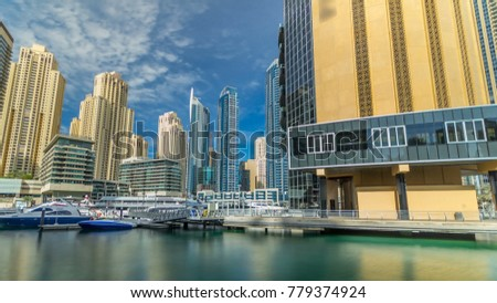 View on Dubai Marina from pier with floating yachts and boats. Timelapse hyperlapse of business city in Dubai at waterfront, UAE #779374924