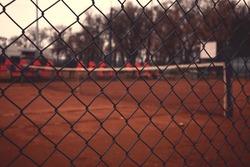 View on empty tennis yard through fence.