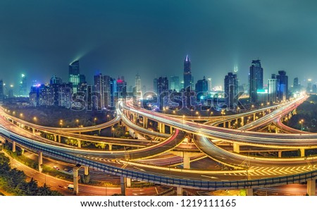 View on famous highway intersection in Shanghai, China, with illuminated highways and skyscrapers.  #1219111165