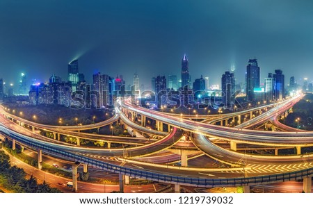 View on famous highway intersection in Shanghai, China, with illuminated highways and skyscrapers.  #1219739032