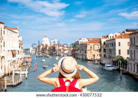 View on Grand canal with woman traveler in hat on Academia bridge in Venice. Back view with copy space #430077532