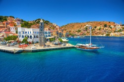 View on Greek sea Symi island harbor port, classical ship yachts, houses on island hills, tourists Aegean Sea bay. Greece islands holidays vacation travel tours from Rhodos island. Greece architecture