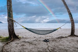 View on hammock between two palm trees on the beach with with rainbow colors after rain