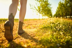 View on legs and shoes of walking girl in the green orchard by the path, during sunny day.