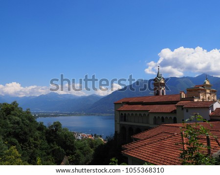 View on Madonna del Sasso Church above Locarno swiss city, alpine Maggiore lake at canton Ticino in Switzerland, mountainside landscapes, cloudy blue sky in 2017 warm sunny summer day, Europe on July #1055368310
