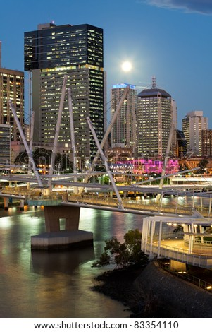 view on modern pedestrian bridge in dense city at night (brisbane, queensland,australia)