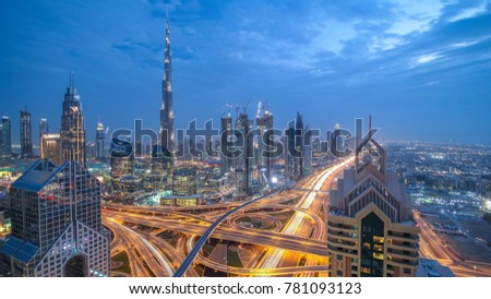 View on modern skyscrapers and busy evening highways day to night transition timelapse in luxury downtown of Dubai city. Top aerial view from tower rooftop. Road junction traffic. Dubai, United Arab #781093123