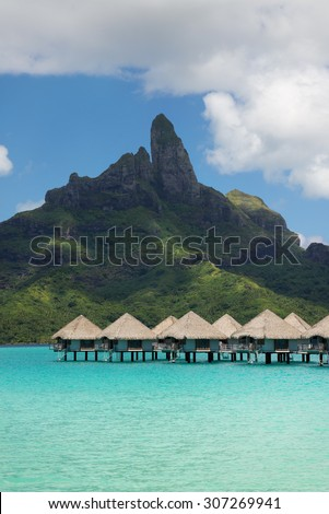 view on Mount Otemanu through turquoise lagoon and overwater bungalows on the tropical island Bora Bora, honeymoon destination, near Tahiti, French Polynesia, Pacific ocean