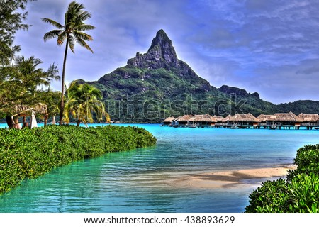 View on Mount Otemanu through turquoise lagoon, palms, and overwater bungalows on the tropical island Bora Bora, honeymoon destination, near Tahiti, French Polynesia, Pacific ocean. HDR picture.