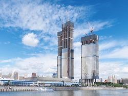 View on office business buildings under construction with working cranes on the roof on river side. Moscow-City business center area. Moscow skyscraper architecture. Blue clouds in the summer sky