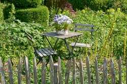 View on old weathered white french bistro table and chairs in a lush garden with old wooden pole fence in front. On the table a pot of purple violets.