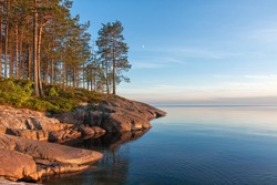 View on Onega Lake granite shore with pines and crescent in sky at midnight sun. Besov Nos cape, Karelia Republic, Russia.